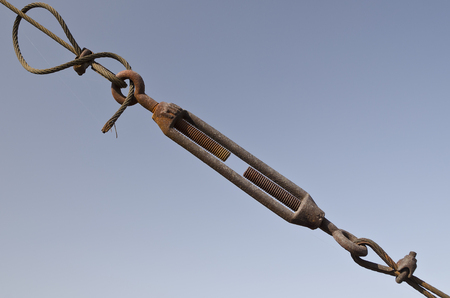 Steel turnbuckle holding hook eye with fastening and metal cables