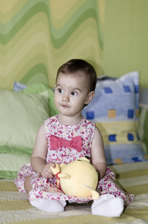 sound therapist: Portrait of a beautiful baby girl sitting on bed