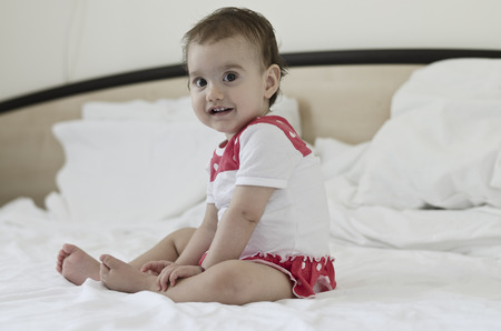 day dream: Portrait of a beautiful baby girl sitting on bed after a day dream