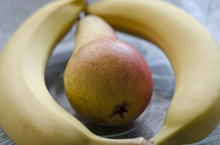 Fruit bowl with two bananas and a pear