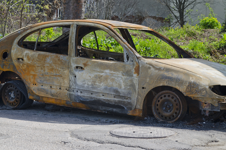 Burned car parked on the street side view - Close up photo of a burned out car Stock Photo