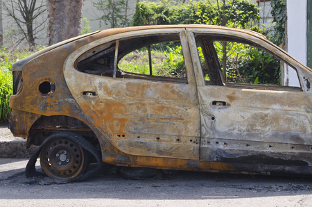 burned out: Burned car parked on the street side view - Close up photo of a burned out car Stock Photo