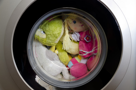 Washing machine door with rotating toys inside Stock Photo