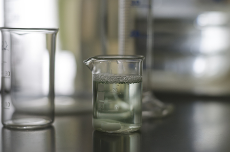 Sample of water in glass tube with green coloring gradient Imagens