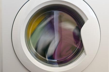 Puerta de la lavadora con prendas giratorias en el interior