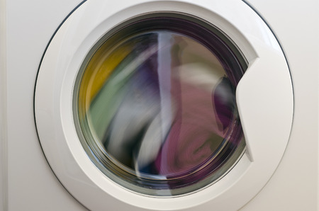 Waschmaschinentür mit rotierenden Kleidungsstücken im Inneren
