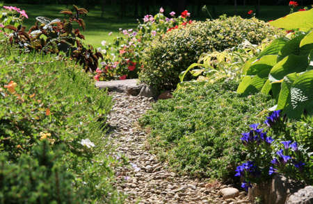 A stone walkway winding its way through a tranquil garden Stock Photo - 6616203
