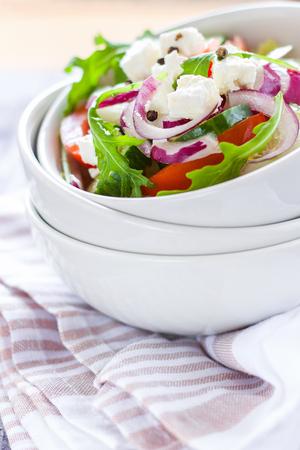 textil: Greek salad in white ceramic bowl on textil napkin Stock Photo