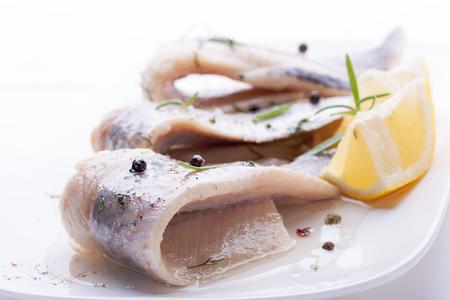 Herring with salt, pepper, herbs and lemon on white ceramic plate on white background Stockfoto