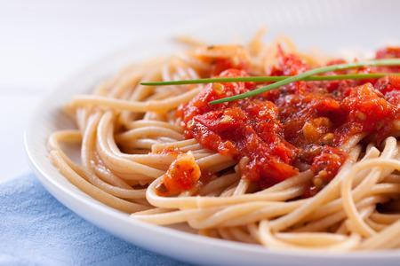 Espaguetis con salsa de tomate y cebollas de primavera en la placa de cerámica blanca Foto de archivo - 47253750