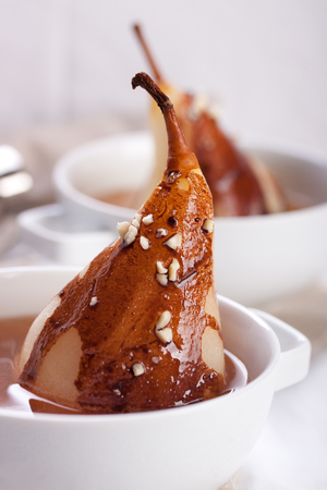 confiserie: Pear poached in white wine with chocolate sauce and nuts for Christmas Stock Photo
