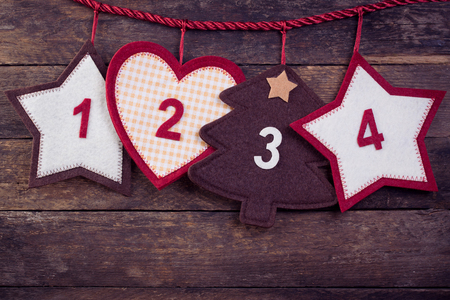 adviento: Advent calendar on an old wooden background. Toned