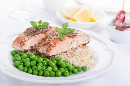 흰색 배경에 흰색 세라믹 접시에 쌀, 녹색 완두콩, 향미료와 구운 된 연어 스톡 콘텐츠