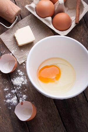 cook: Ingredients and tools ready to make a cake, flour, eggs, butter, cinnamon stick on a wooden table