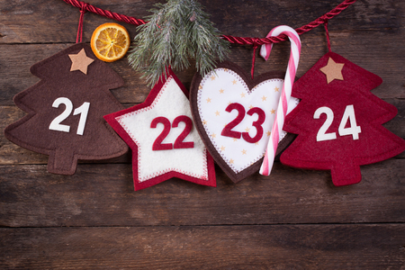 24 month old: Advent calendar with fir and candy cane on an old wooden background