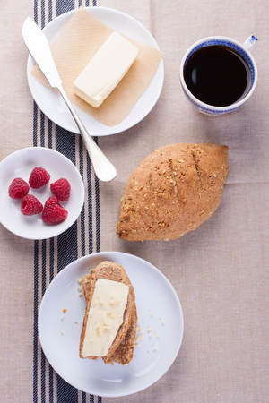 party table: Homemade oatmeal bread on a wooden table with coffee, butter and raspberries for breakfast. Topview