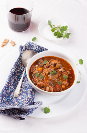 Chicken ragout with pumpkin, mushrooms and oregano stewed in red wine in a white ceramic bowl. Selective focus
