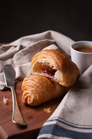 buttery: Closeup of croissant with jam and coffee on a wooden background Stock Photo