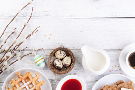 Easter breakfast with quail eggs, waffles, fruit jam, milk, coffee and sandwiches, with willow branch on a white wooden background, top view with copy space