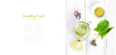 Healthy green smoothie with spinach, kiwi, banana, chia seeds, lime and green tea matcha in a glass jar on a white wooden background with copy space, top view