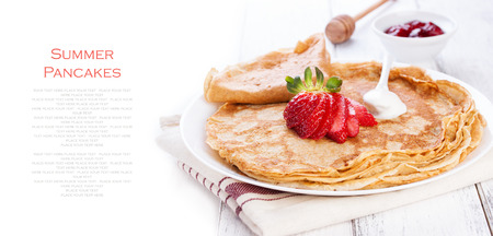 pancake week: Staple of wheat golden yeast pancakes or crepes, traditional for Russian pancake week, with fresh strawberry on a wooden table on a white background with place for text or copy space, top view
