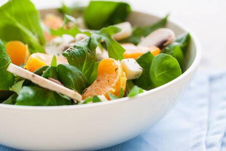 sommer: Sommer salad with rocket salad, mandarin, mushrooms and cheese gorgonzola in a white ceramic bowl , closeup