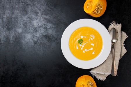 Homemade creamy pumpkin soup with cream and parsley in a white ceramic plate, top view with copy space Stockfoto