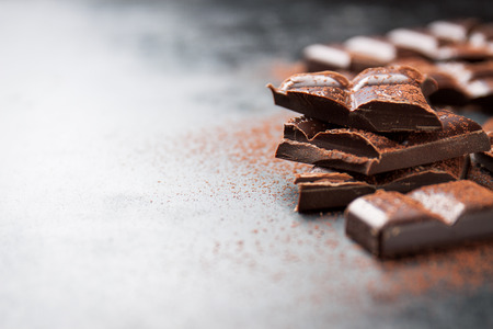 dark chocolate: Dark chocolate on a dark background, closeup with place for text, selective focus Stock Photo