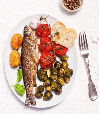 stuffed fish: Homemade stuffed and grilled fish with baked vegetables and bread, top view Stock Photo