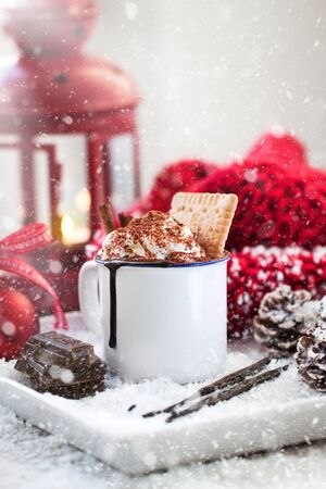 Homemade christmas hot chocolate with whipped cream, cacao and cinnamon on a plate in christmas holiday atmosphere