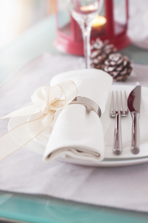 Elegant decorated Christmas table setting with modern cutlery, napkin, bow and christmas decorations. Christmas menu concept, closeup Stock Photo