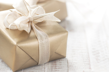Golden gift boxes with beautiful ribbon and bow on a bright shiny background, holiday concept, horizontal with copy space