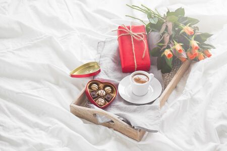 Romantic breakfast with coffee, chocolate pralines, gift box and pretty bouquet of roses, valentine's day or holiday concept