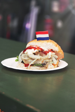 Netherlandish or dutch fish burger sandwich with fresh hering, onion, ketchup and mayonnaise. Street food or unhealthy food concept Stock Photo