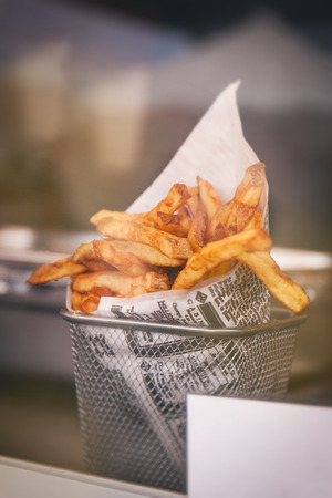 Pommes frites or french fries behind the counter window, ready to eat. Street food or unhealthy food concept