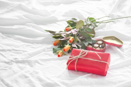 Beautiful colorful pretty gift or present in a paper with chocolate pralines, coffee and fresh roses on a bed. Holiday, valentines day, birthday or surprise concept