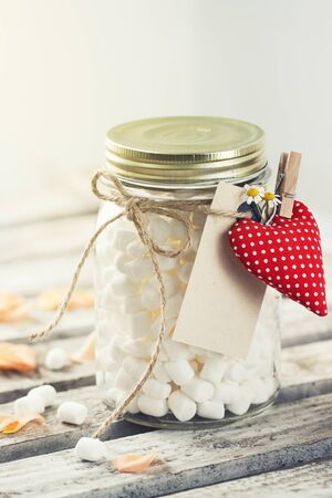 Jar with marshmallow and red plush heart. Love, sweet or valentines day concept, vintage toning