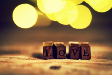 revelation: Love or Valentines Day Concept with Wooden Letters LOVE on a wooden background.