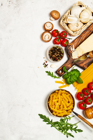 Italian food or ingredients background with fresh vegetables, pasta, cheese parmesan and spices. Top view, view from above. Copy space.