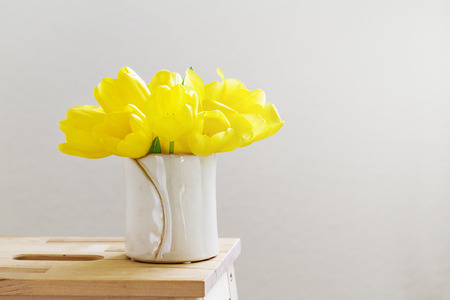 Beautiful Fresh Spring Yellow Tulips in Vase on bright background. Spring, easter or Mothers Day Concept.