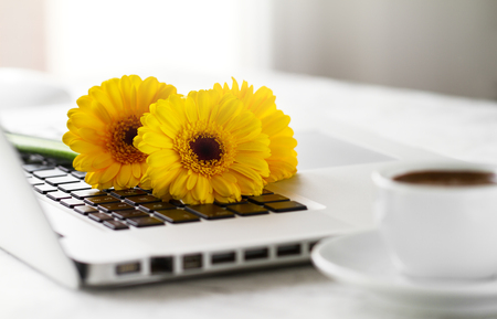 Working space or working place with laptop, flowers and coffee on bright background. Horizontal with copy space. Spring or business concept. Standard-Bild