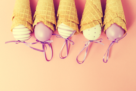 Colorful Ice Cream Cones with Easter Eggs on Pink Background. Vanilla or Pastel Toning. Minimalism. Flat Lay.  Stock Photo