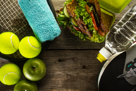 Healthy Life Sport Concept. Sneakers with Tennis Balls, Towel, Apples, Healthy Sandwich and Bottle of Water on Wooden Background. Copy Space. Above. Stock Photo