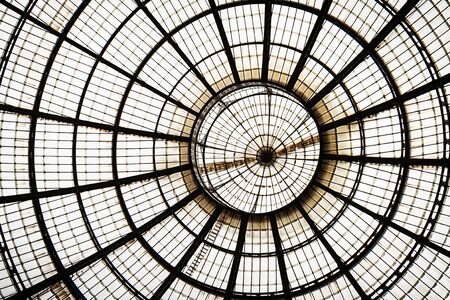 Closeup of a glass roof with metal frame circle and lines. Indoors. Daylight. Background glass graphic architecture elements. Milan, Italy.