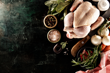From above shot of uncooked turkey composed with cooking ingredients and spices on black surface.  Stock Photo