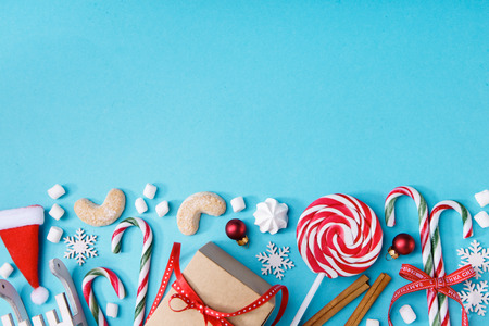 Blue background with composed variety of sweet decor for Christmas holiday.