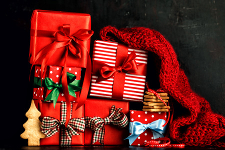 Various wrapped giftboxes decorated with ribbons and arranged with cookies and scarf on black backdrop.  Stock Photo