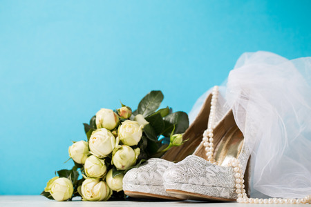 Lace high heels and pearl necklace arranged with bouquet and veil on blue studio background.