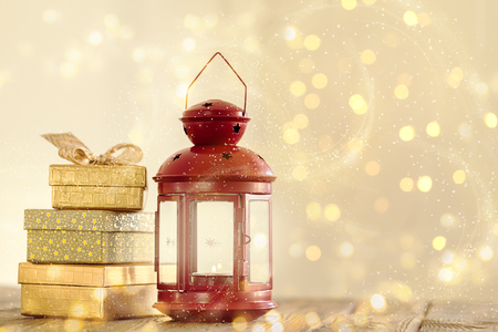 Arranged stack of shiny Christmas gifts and red lantern with burning candle in golden sparkles.  Banco de Imagens