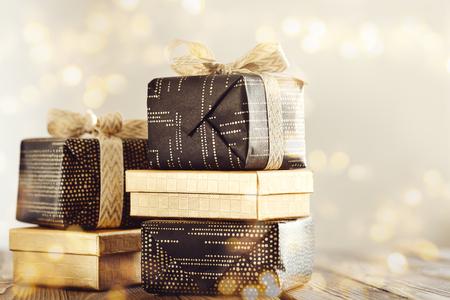 Arreglo de regalos envueltos con cintas en brillos dorados.